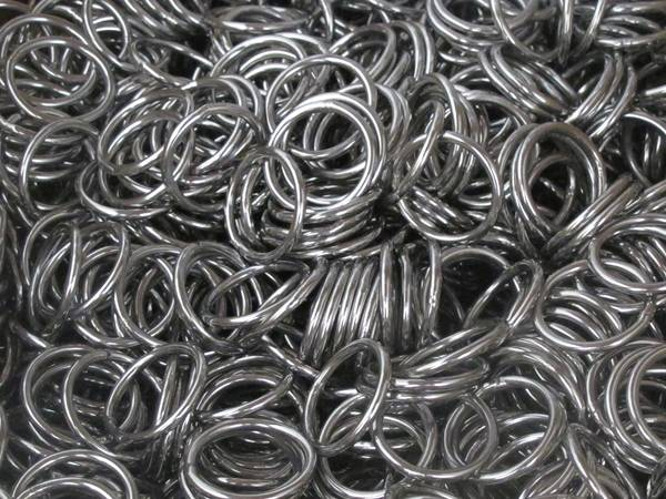 Many stainless steel round rings in a box for wire rope.